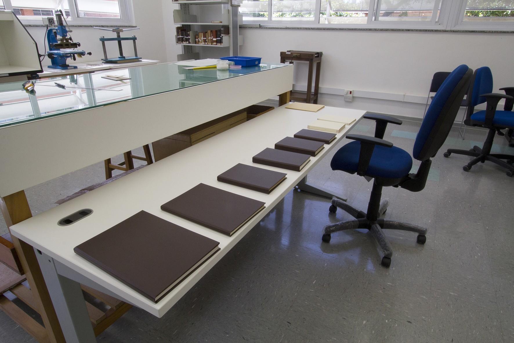 Bancada com capas de livros em processo de restauração na Oficina de  #384663 1772x1181