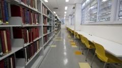 Corredor com estantes de livros e mesas para leitura na Nova Biblioteca da Faculdade de Educação (FEUSP). Foto: Marcos Santos / USP Imagens
