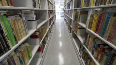 Corredor e estantes com livros da coleção da Nova Biblioteca da Faculdade de Educação (FEUSP). Foto: Marcos Santos / USP Imagens