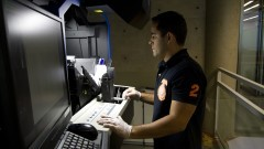 Operador técnico operando o sistema  Robokabis III que utiliza duas câmeras de alta resolução que capturam duas páginas simultaneamente. Foto: Marcos Santos/USP Imagens