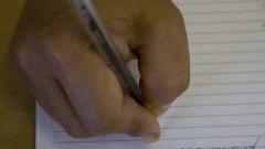Mão escrevendo. Foto: Marcos Santos/USP Imagens