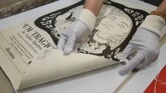 Funcionária mostra detalhes de antigo cartaz teatral do acervo do Laboratório sobre o Teatro Paulista