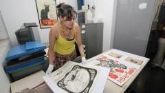 Funcionária mostra de antigo cartaz teatral do acervo do Laboratório sobre o Teatro Paulista