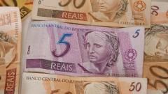 Cédula de R$ 5,00 (cinco reais) centralizada em meio a outras cédulas de R$ 50,00 (cinquenta reais). Foto: Marcos Santos / USP Imagens