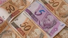 Cédula de R$ 5,00 (cinco reais) contrastando com várias cédulas de R$ 50,00 (cinquenta reais). Foto: Marcos Santos.