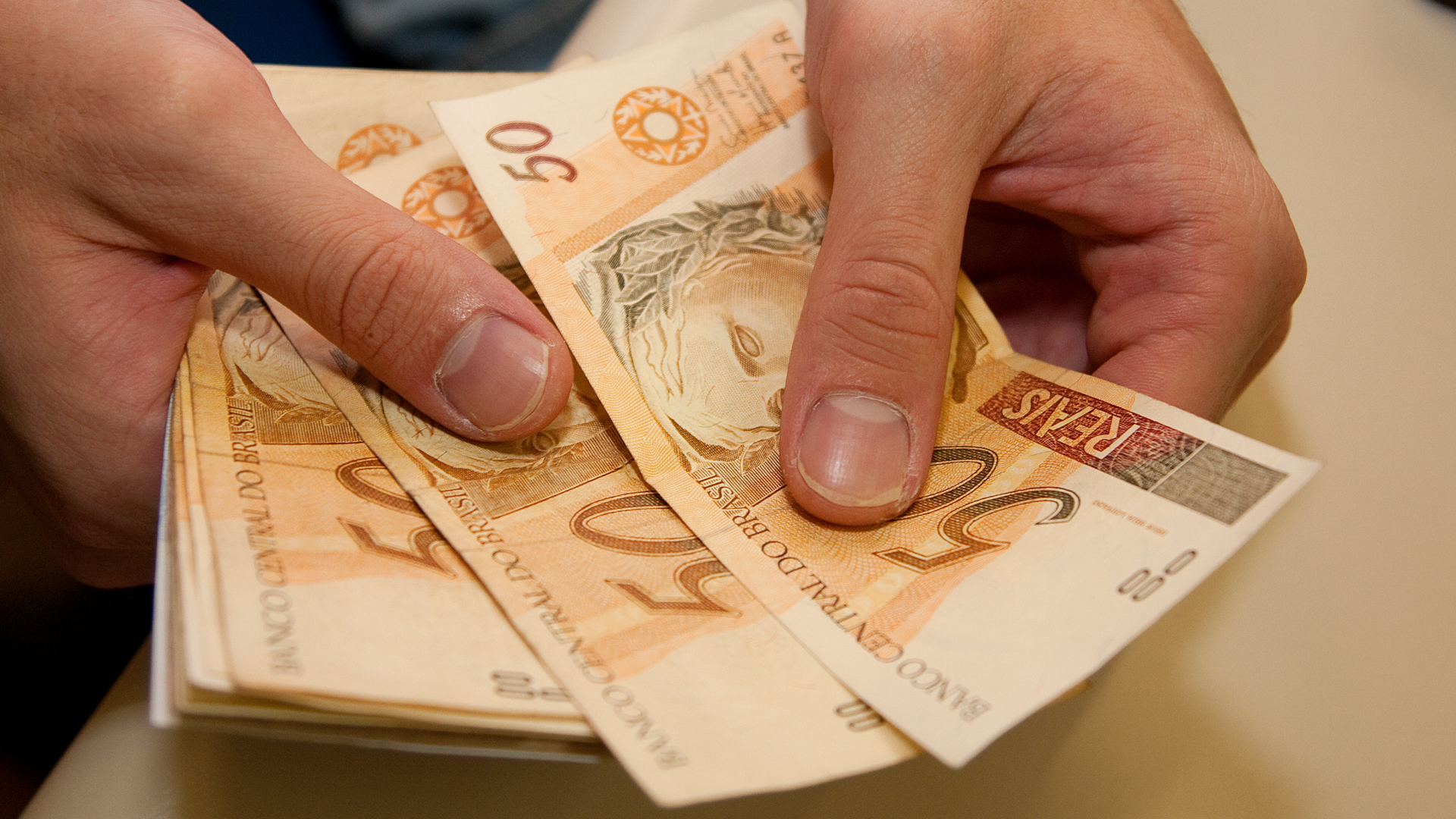 Manuseio de dinheiro: Cédulas de Real sendo contadas.