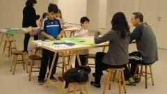 """Detalhe de crianças e adultos à mesa na atividade """"Histórias da Arte para crianças: entre livros e obras"""". Foto: Juliana Pinheiro Prado / USP Imagens"""