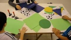 """Detalhe de crianças sentadas à mesa na atividade """"Histórias da Arte para crianças: entre livros e obras"""". Foto: Juliana Pinheiro Prado / USP Imagens"""