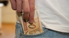 Pessoa retira dinheiro do bolso. Cédulas de R$ 50,00 (cinquenta reais). Cédulas de real sendo retiradas do bolso. Foto: Marcos Santos.