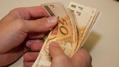 Pessoa manuseando dinheiro, contando cédulas de R$ 50,00 (cinquenta reais). Foto: Marcos Santos / USP Imagens