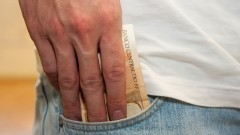 Pessoa guardando dinheiro no bolso. Cédulas de R$ 50,00 (cinquenta reais). Cédulas de real sendo guardadas no bolso. Foto: Marcos Santos / USP Imagens
