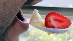 Detalhe de pessoa comendo salada de frutas com colher de plástico - Foto: Pedro Bolle / USP Imagens
