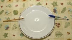 Detalhe de prato branco, com caneta e lápis apoiados na borda, sobre uma mesa. Foto: Marcos Santos / USP Imagens