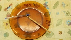 Detalhe de prato, com caneta e lápis dentro, sobre uma mesa. Foto: Marcos Santos / USP Imagens