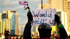 """Manifestante com flores e cartaz """"World Help us"""". George Campos / USP Imagens"""