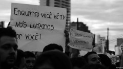 """Cartaz """"Enquanto você vê TV, nós lutamos por você"""". George Campos / USP Imagens"""
