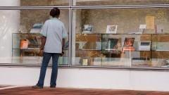 Funcionária olhando a vitrine da Livraria João Alexandre Barbosa, da EDUSP.