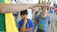 Detalhe de crianças observando bicho-pau no braço de monitor durante a Virada Científica 2015. Foto: Marcos Santos/USP Imagens