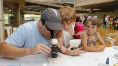 Detalhe de adulto e crianças interagindo com microscópio durante oficina no Ciclo Multidisciplinar 1 (na Faculdade de Arquitetura e Urbanismo) durante a Virada Científica 2015 (segunda edição) realizada dias 17 e 18 de outubro. Foto: Marcos Santos/USP Imagens
