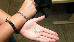 Detalhe de mão segurando moeda de R$ 1,00 (um real). Foto: Marcos Santos / USP Imagens