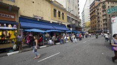 Detalhe de pessoas caminhando, comércios e camelôs na Rua 25 de Março, no Centro de São Paulo. Foto: Pedro Bolle / USP Imagens