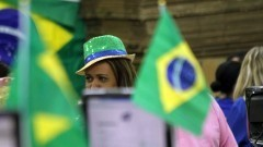 Detalhe de cliente de chapéu entre bandeiras do Brasil. Foto: Pedro Bolle / USP Imagens